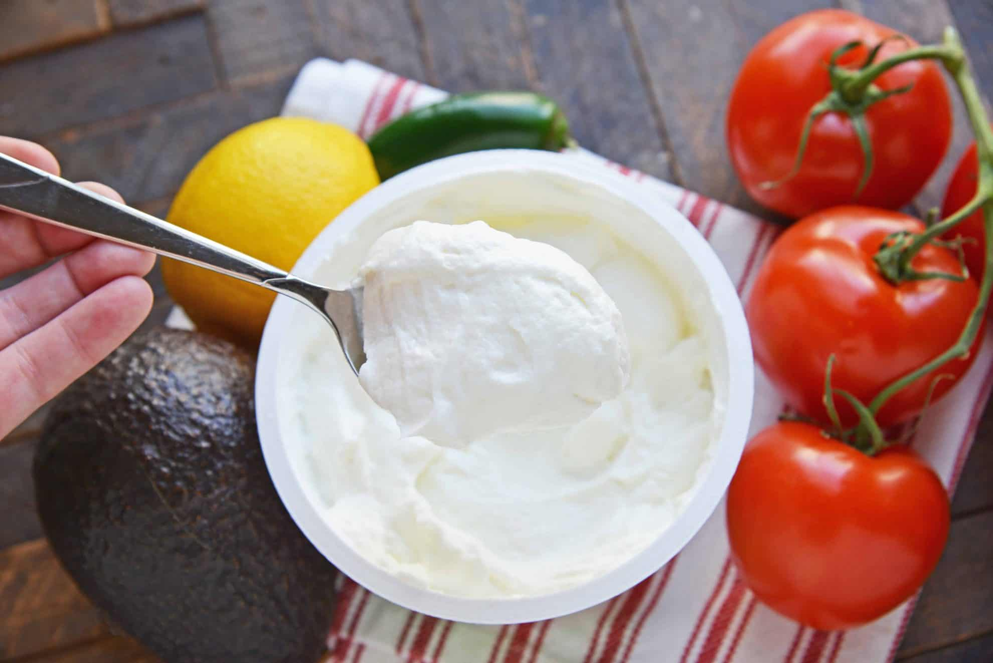 Spoonful of plain yogurt surrounded by fresh vegetables