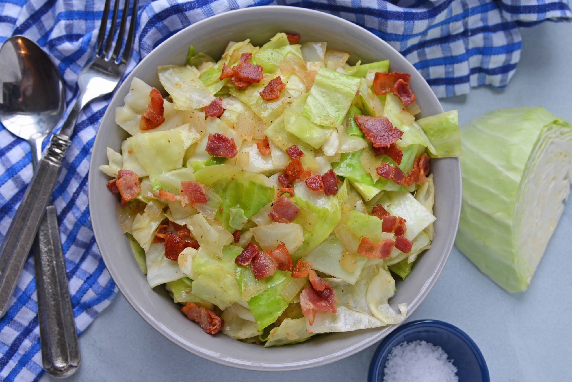 Overhead of bacon fried cabbage with blue napkin