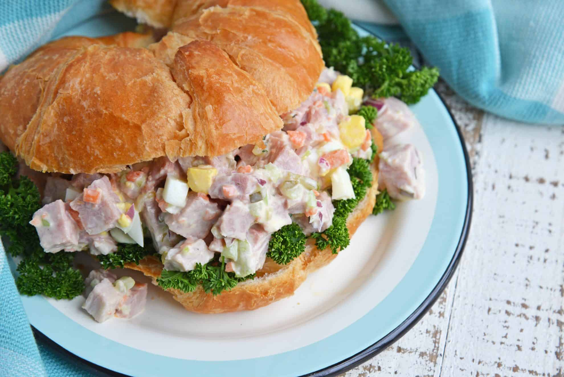 A close up of a sandwich on a plate, with Ham and Salad