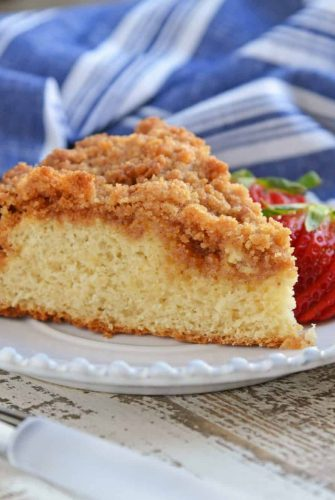 Side view of a coffee cake with sliced strawberries