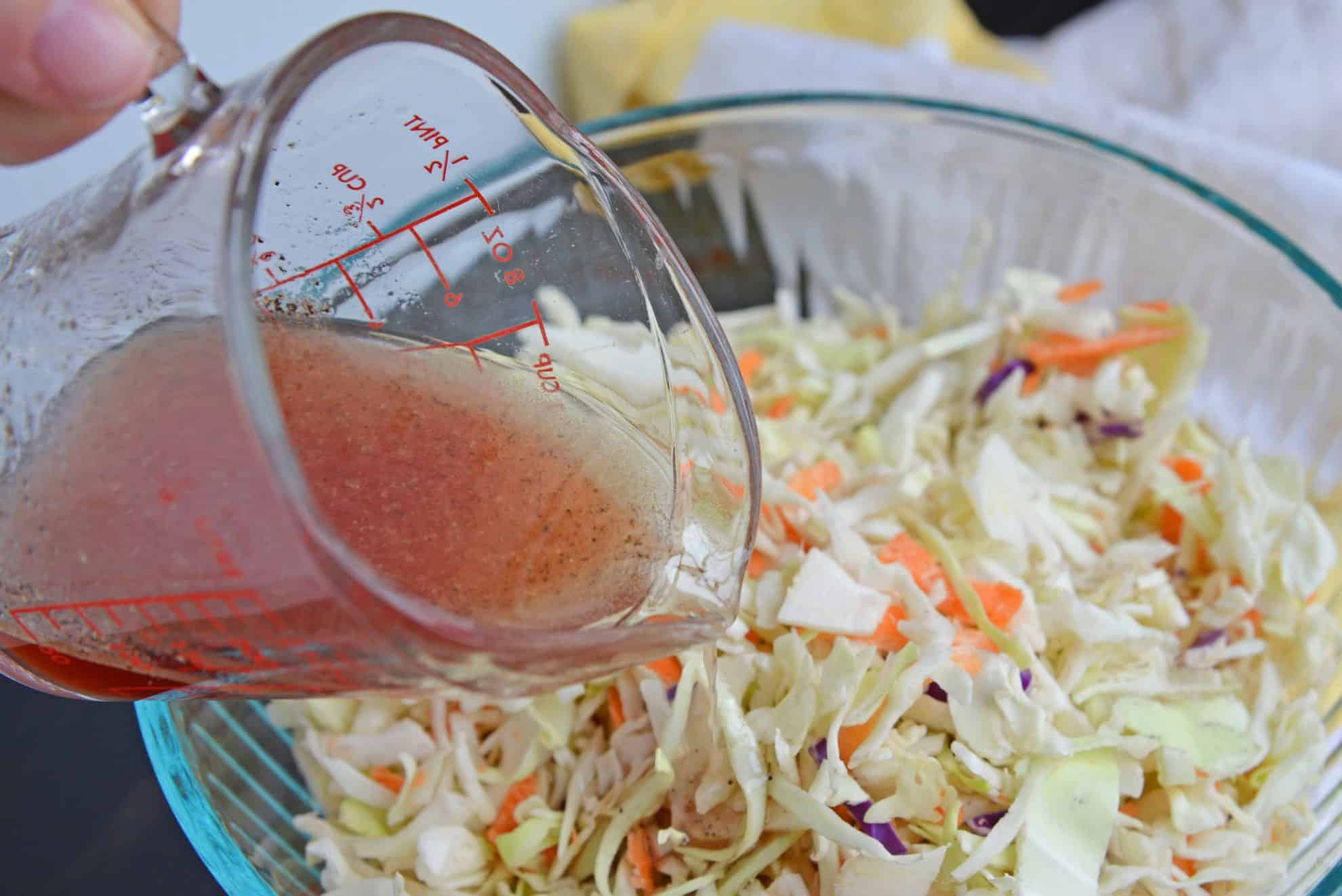 Vinegar dressing pouring over cabbage slaw