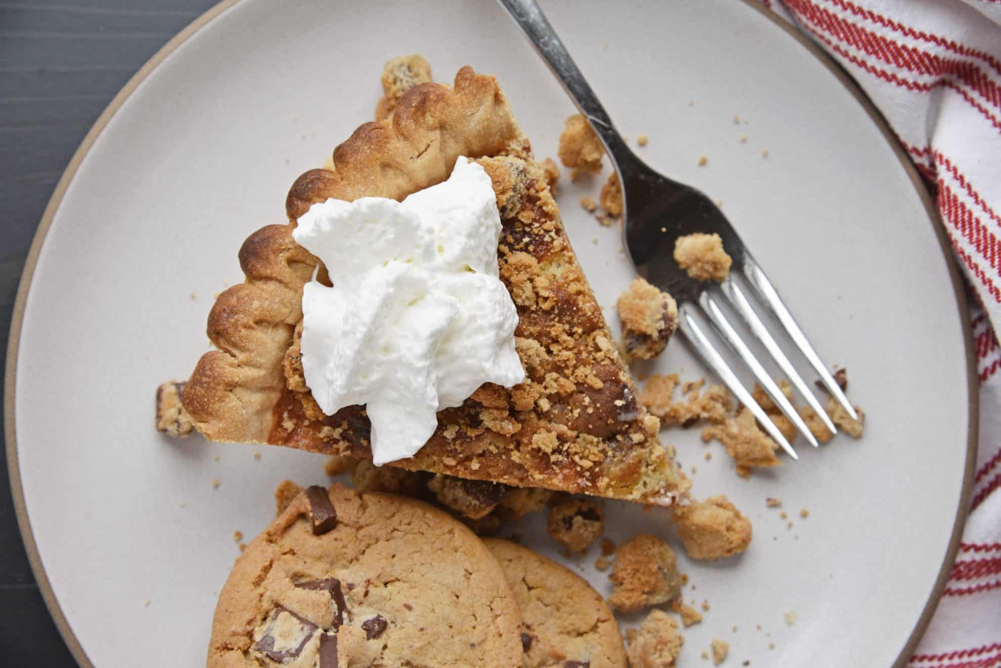 Overhead shot of slice of Chocolate Chip Chess Pie on a white plate with cookie crumbles