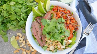 Steak Salad with Green Curry Dressing with cilantro, cashews, red bell pepper, carrots and red onion over romaine lettuce