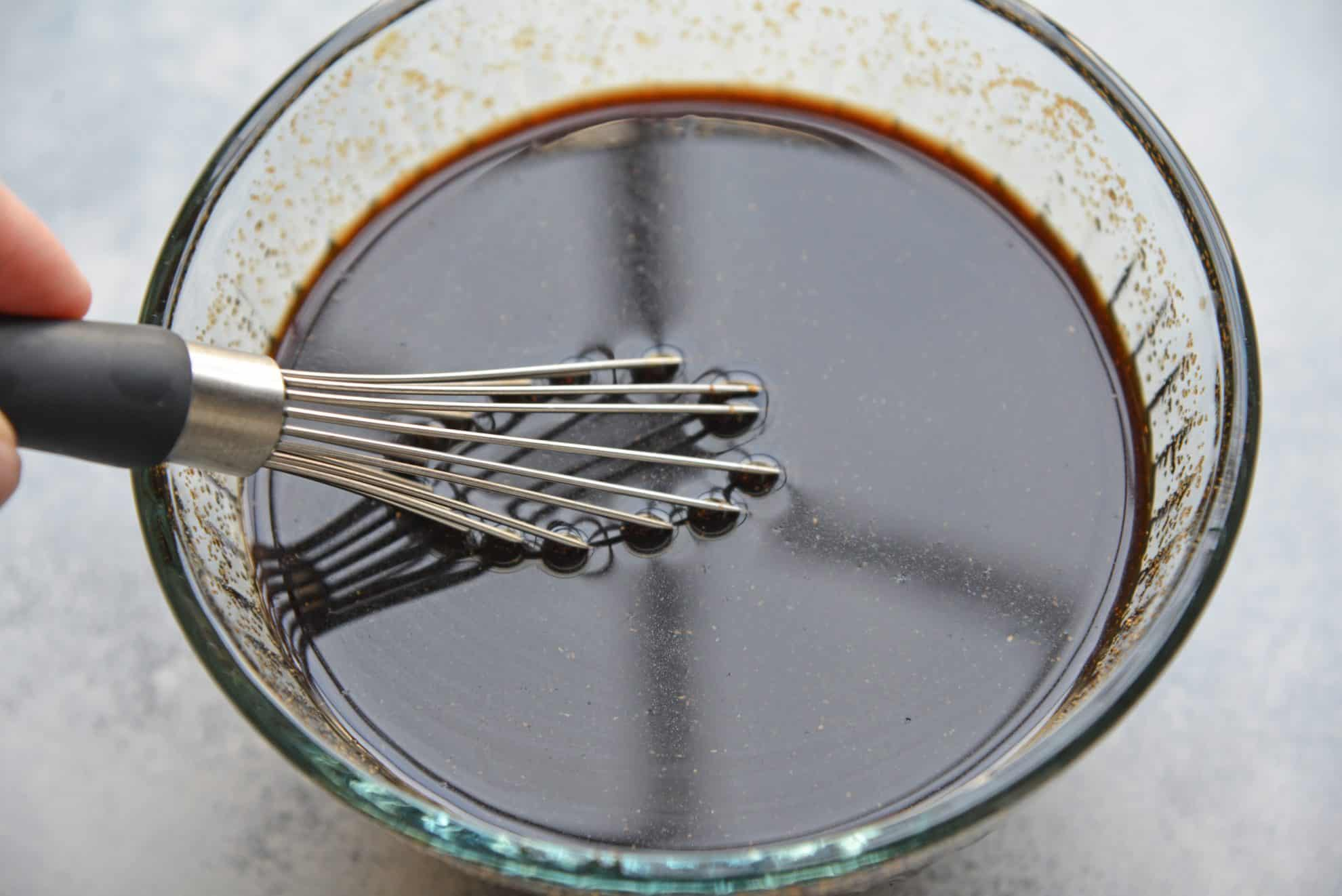 Honey balsamic sauce in a bowl with a whisk