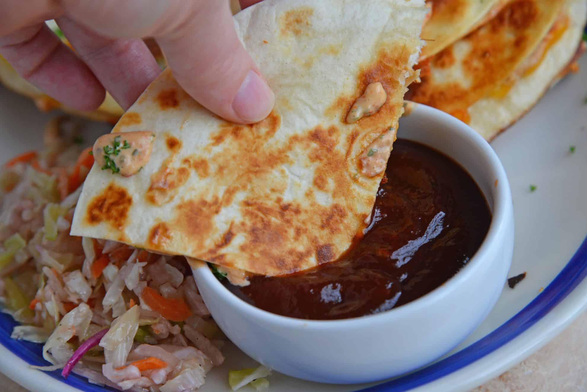 quesadilla dipping into bbq sauce