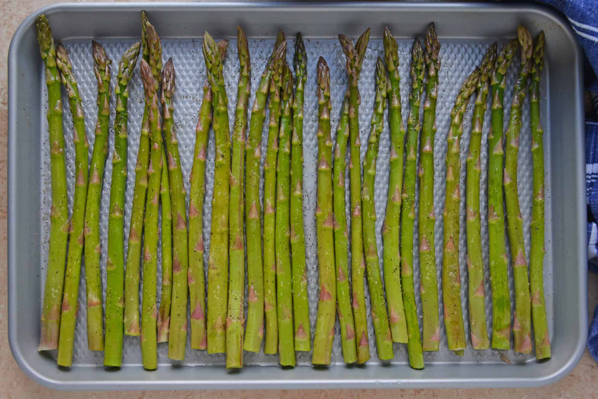 asparagus on a rimmed baking sheet