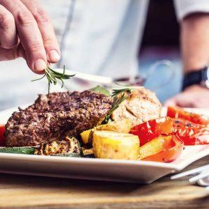 hand garnishing steak with fresh herbs
