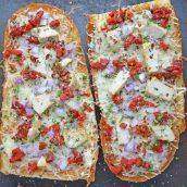 Two french bread pizzas on a baking sheet