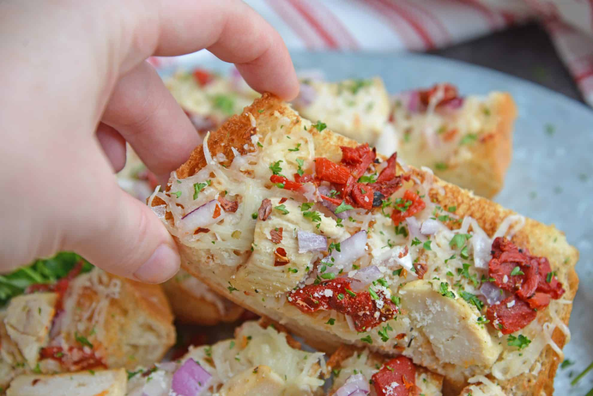hand reaching in for a slice of french bread pizza