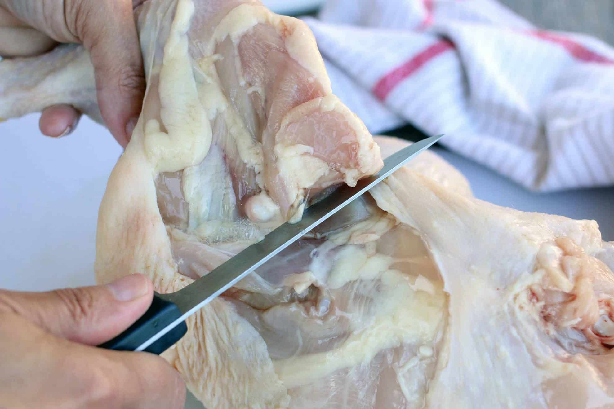 Slicing through the skin to remove the leg quarter from a whole chicken