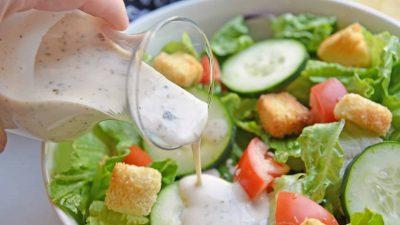 Greek salad dressing pouring over green salad
