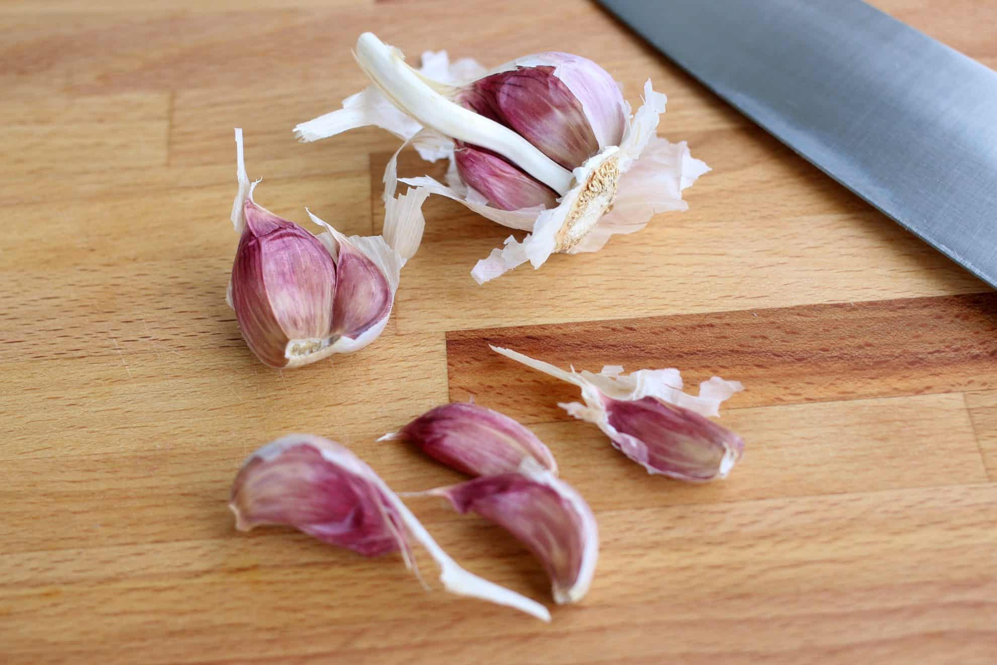 Whole garlic cloves setting on a wooden cutting board alondside a chefs' knife.