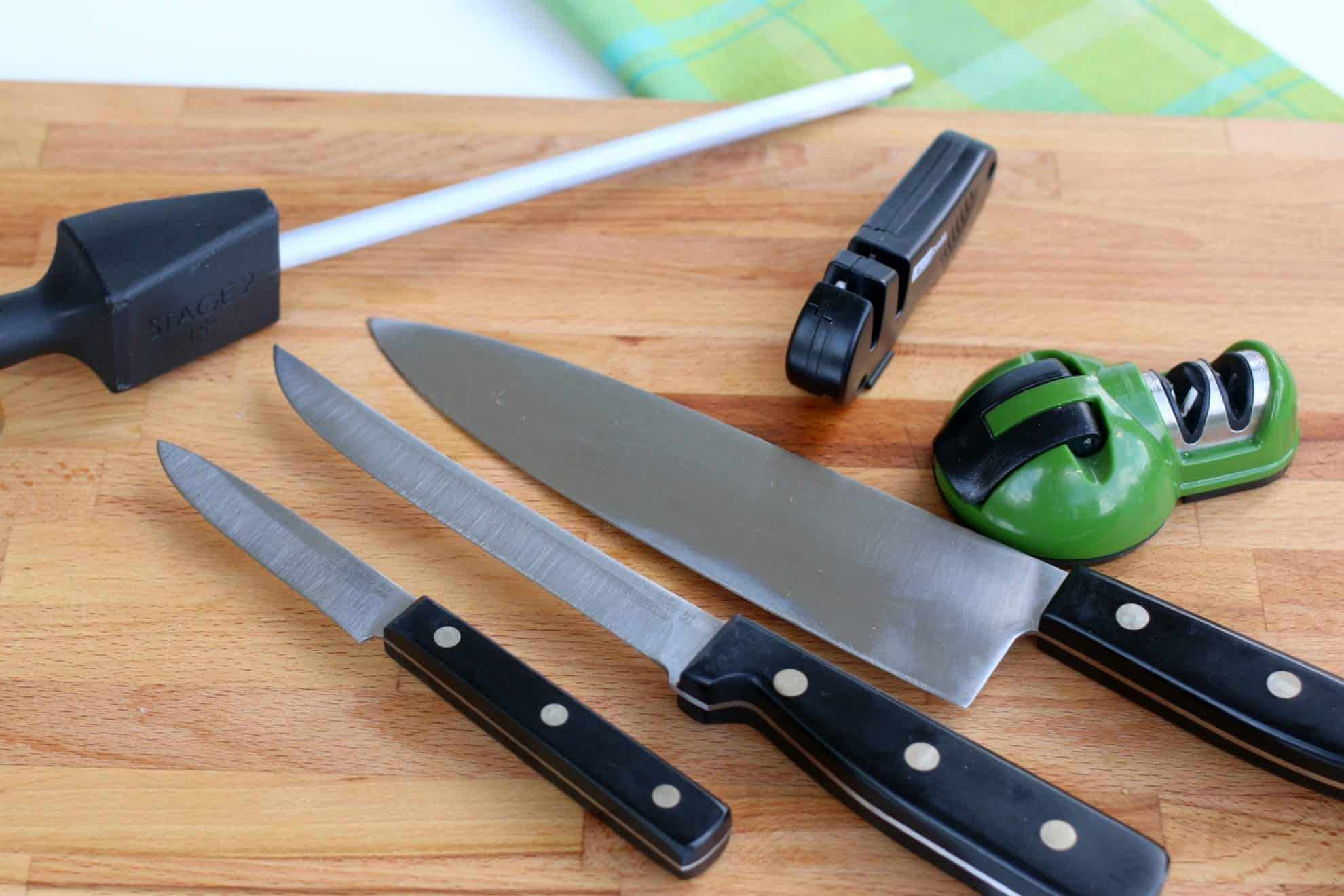 There are many tools for sharpening kitchen knifes. Some are shown here on a cutting board alongside knives.