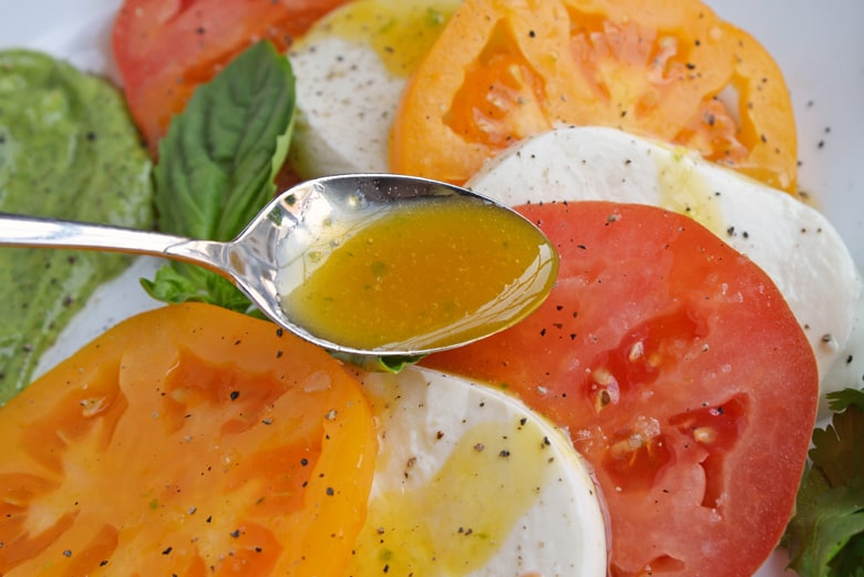 Spooning passion fruit dressing on salad