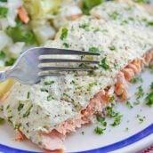 Fork cutting into pesto salmon
