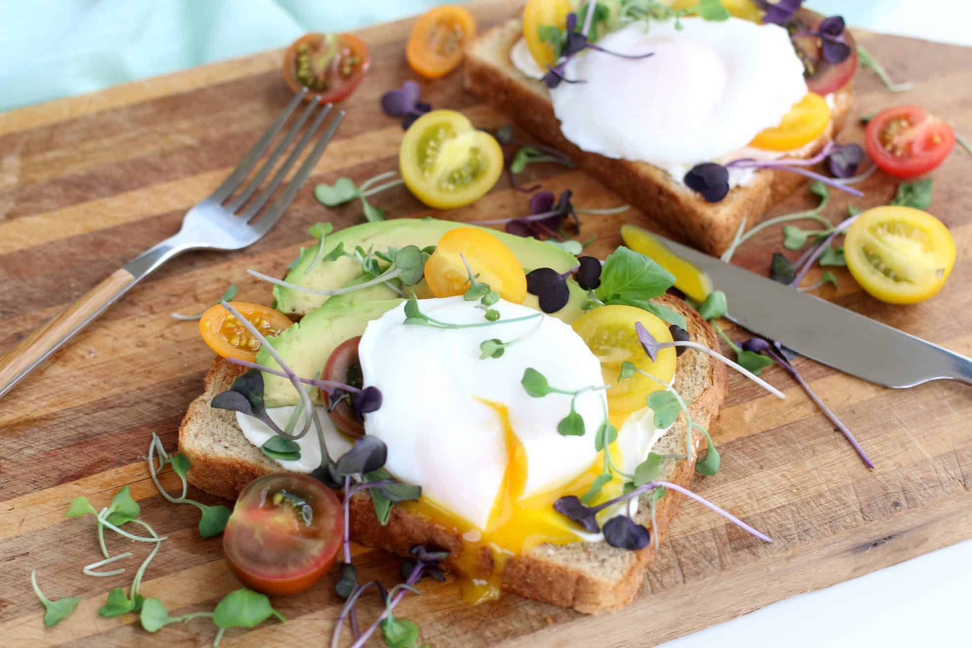 Poached egg on avocado toast garnished with micro greens and heirloom tomatoes