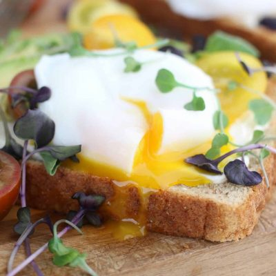 Closeup of a poached egg on avocado toast garnished with micro greens