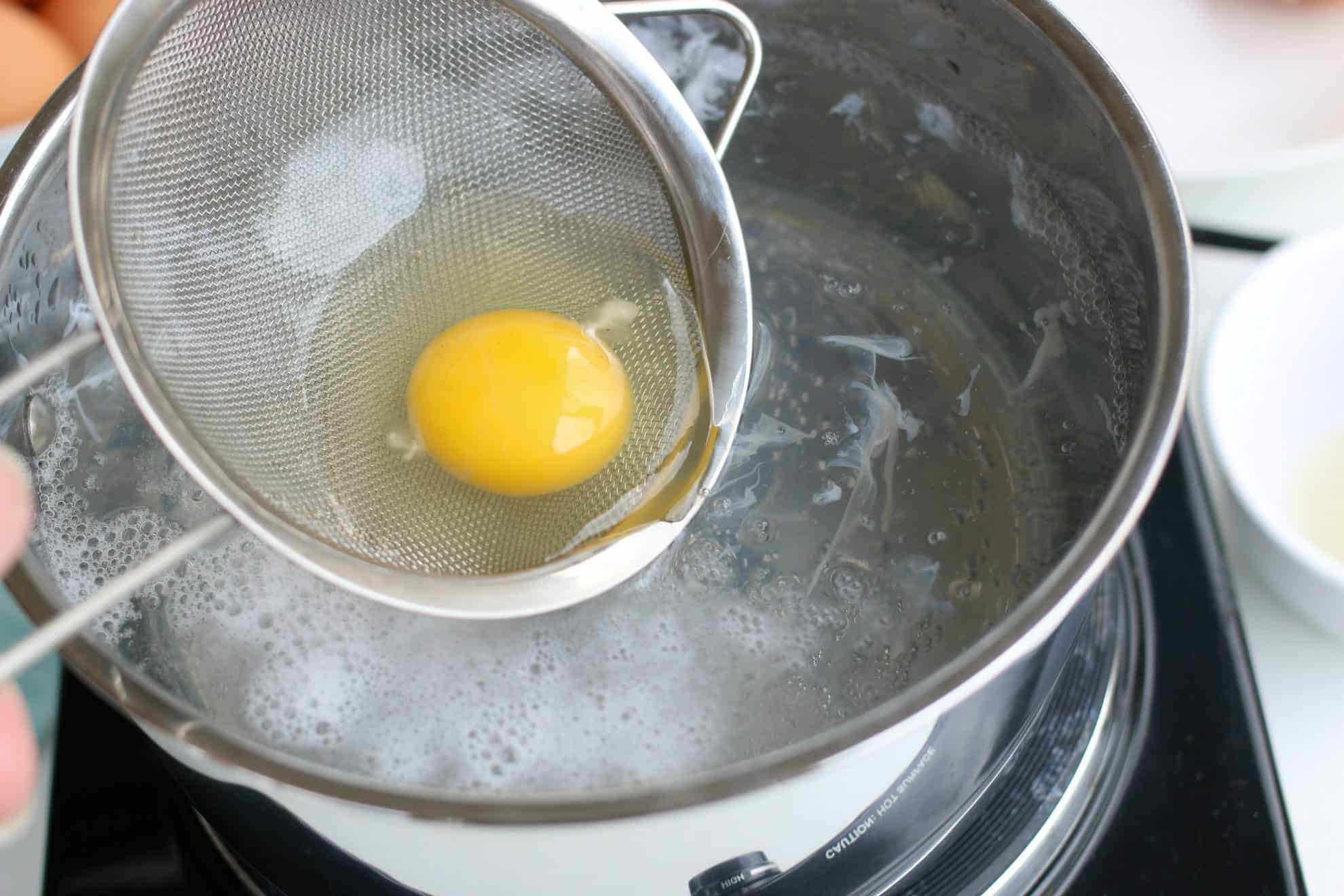 Adding an egg to simmering water to make poached eggs