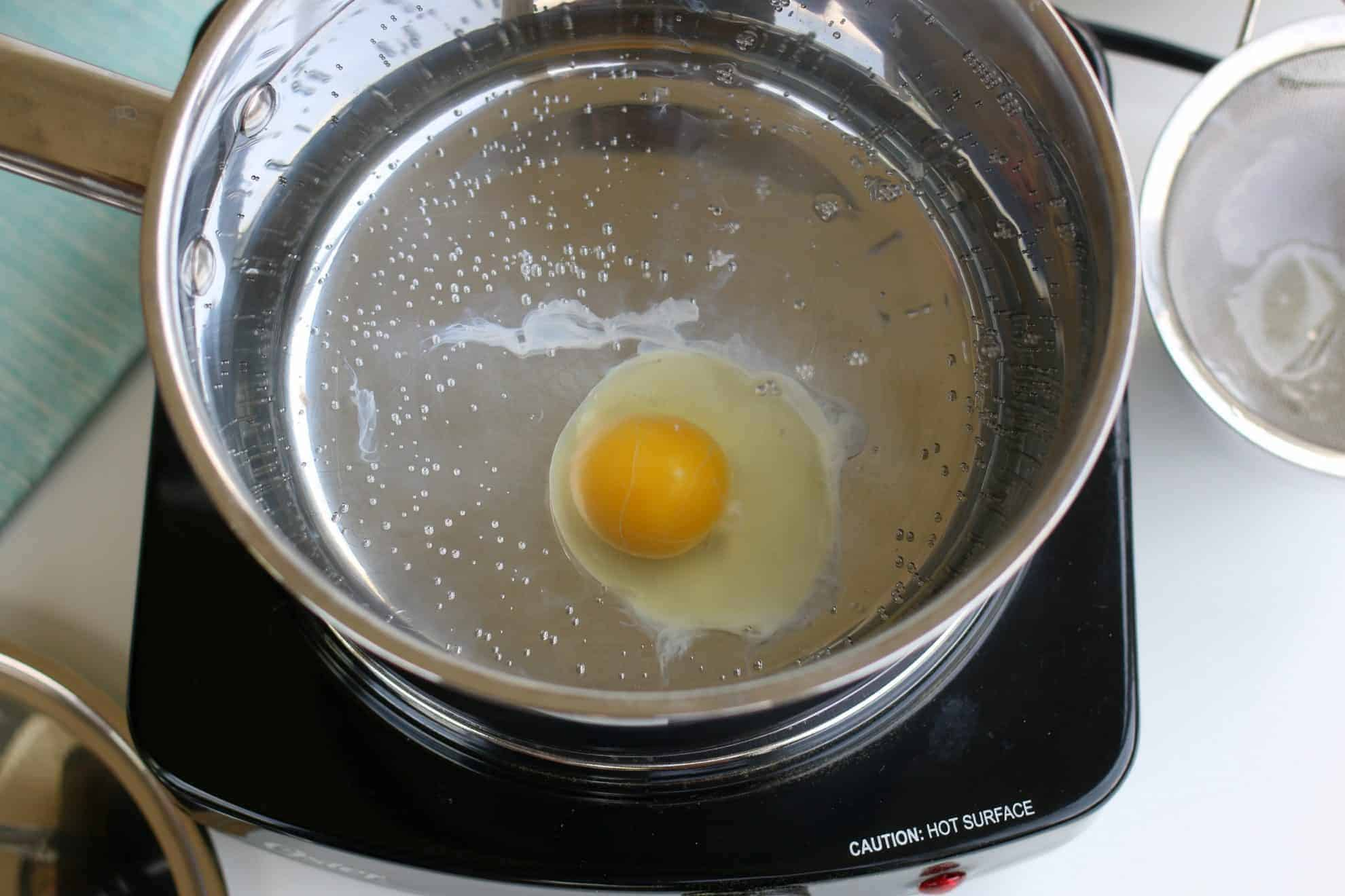 A single egg in a pan of simmering water poaching an egg