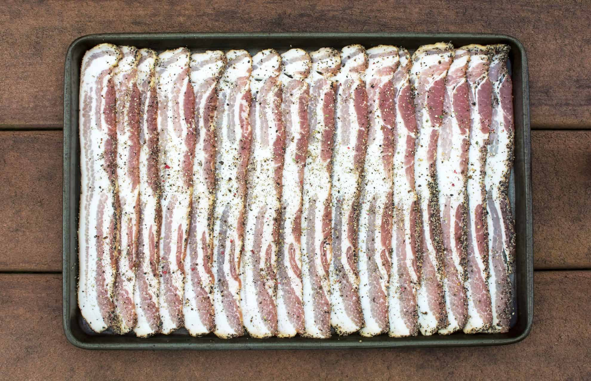 Seasoned uncooked bacon on a baking sheet