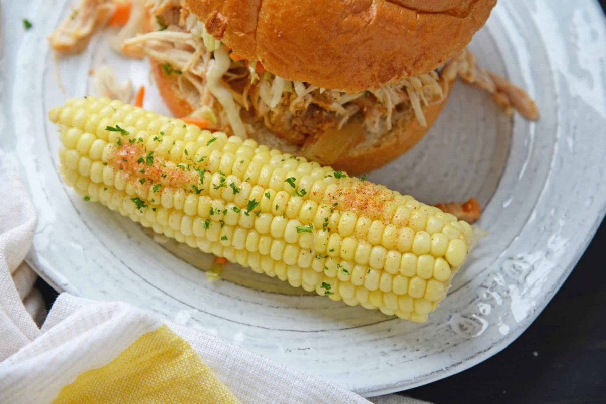 corn on the cob on a white dish with pulled pork sandwich