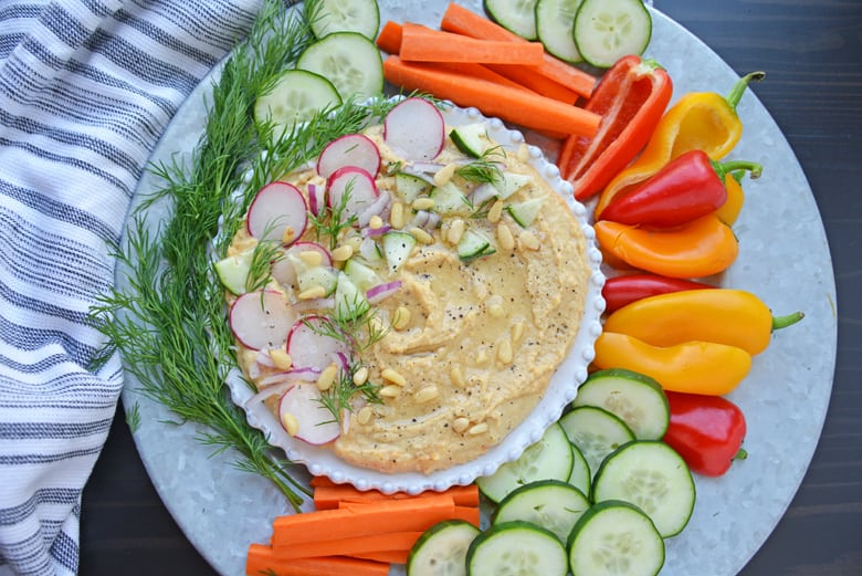 Overhead of hummus with toppings and crudites