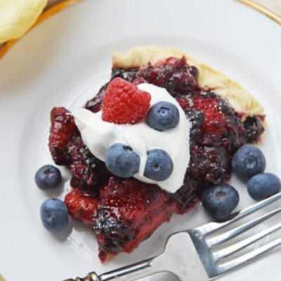 slice of mixed berry pie with whipped cream and cresh berries
