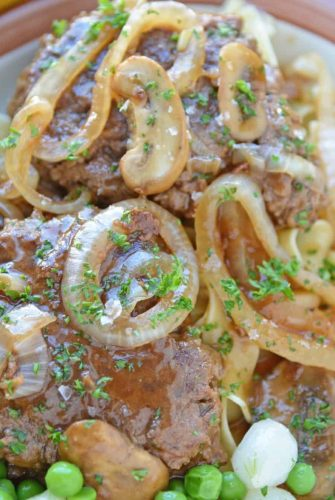 Salisbury steak plated with buttered noodles and peas