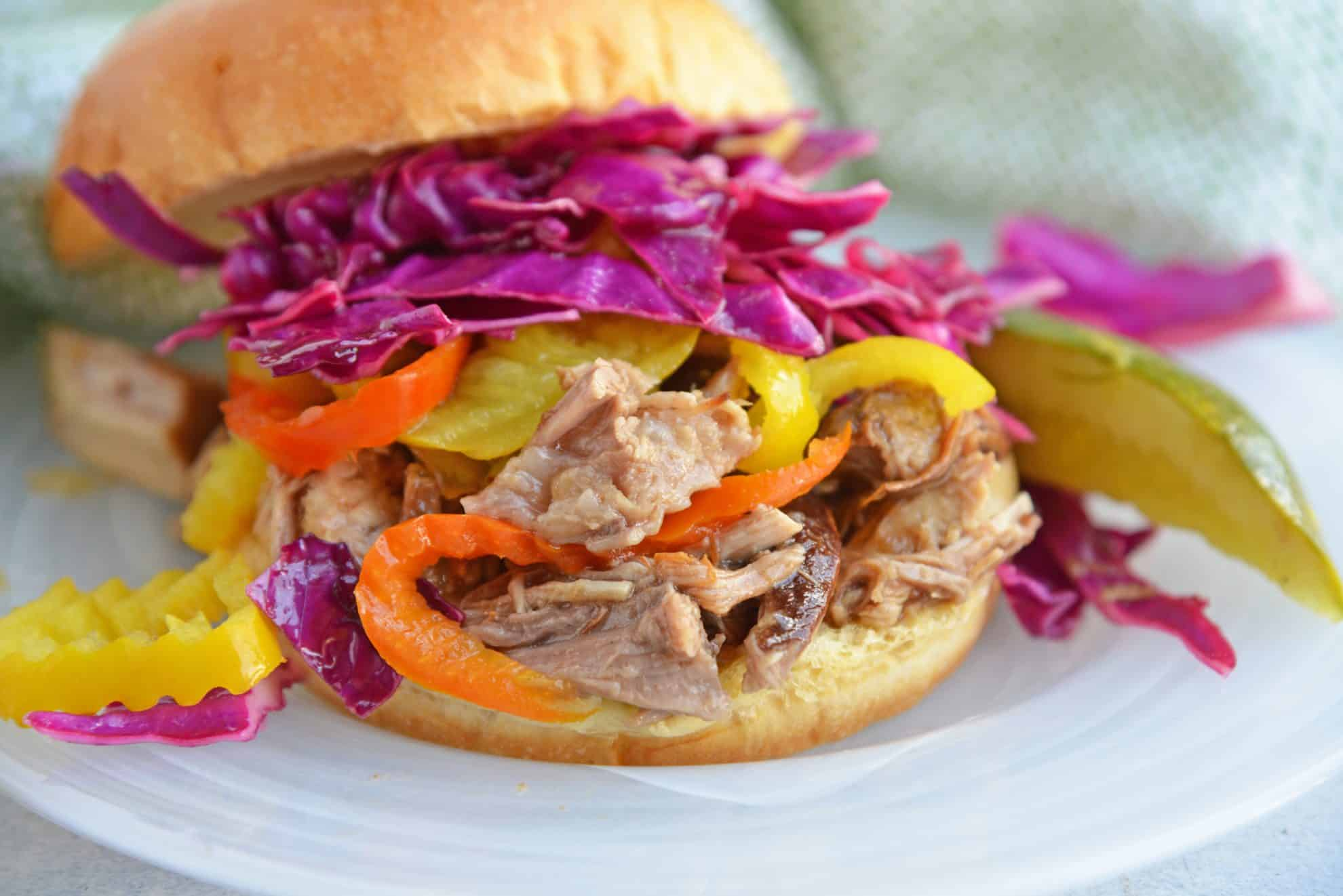 Angle of pulled pork sandwich with red cabbage slaw and pickles