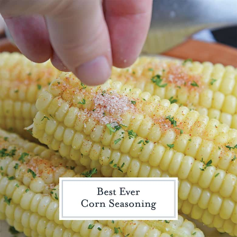sprinkling corn seasoning on an ear of corn