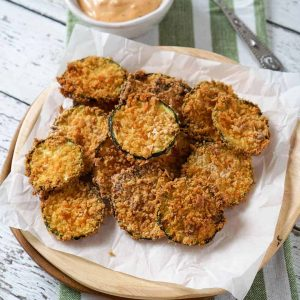 Air fryer zucchini chips on a plate with sauce