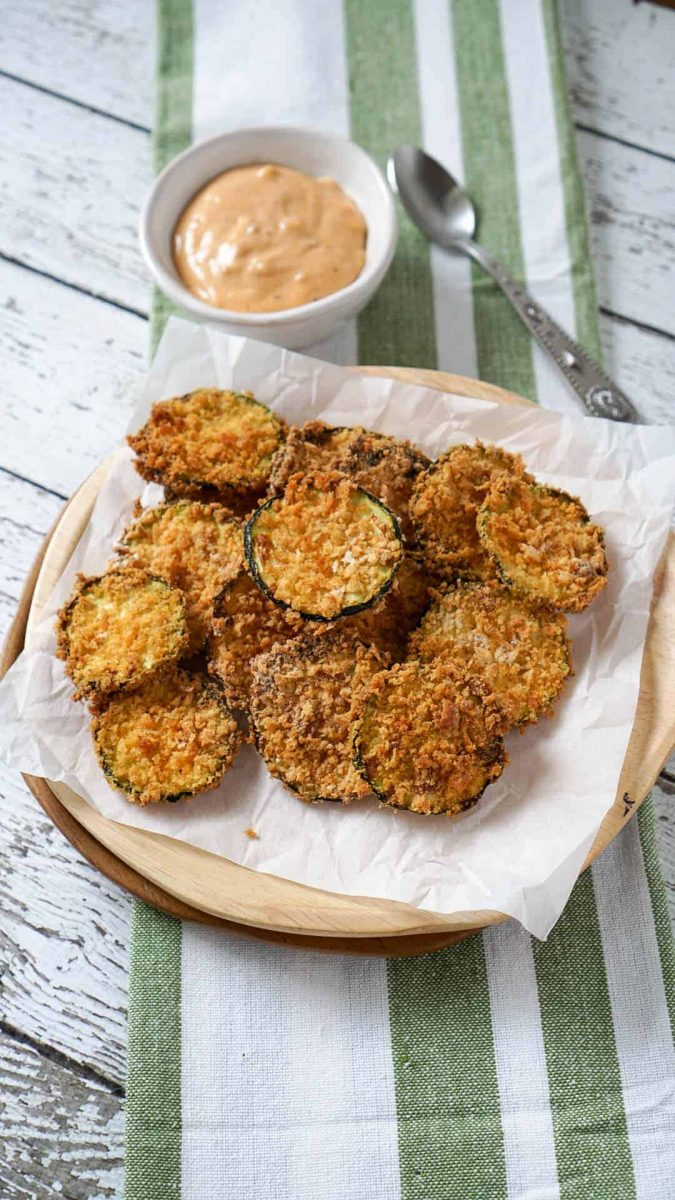 Air fryer zucchini chips on a plate with dipping sauce