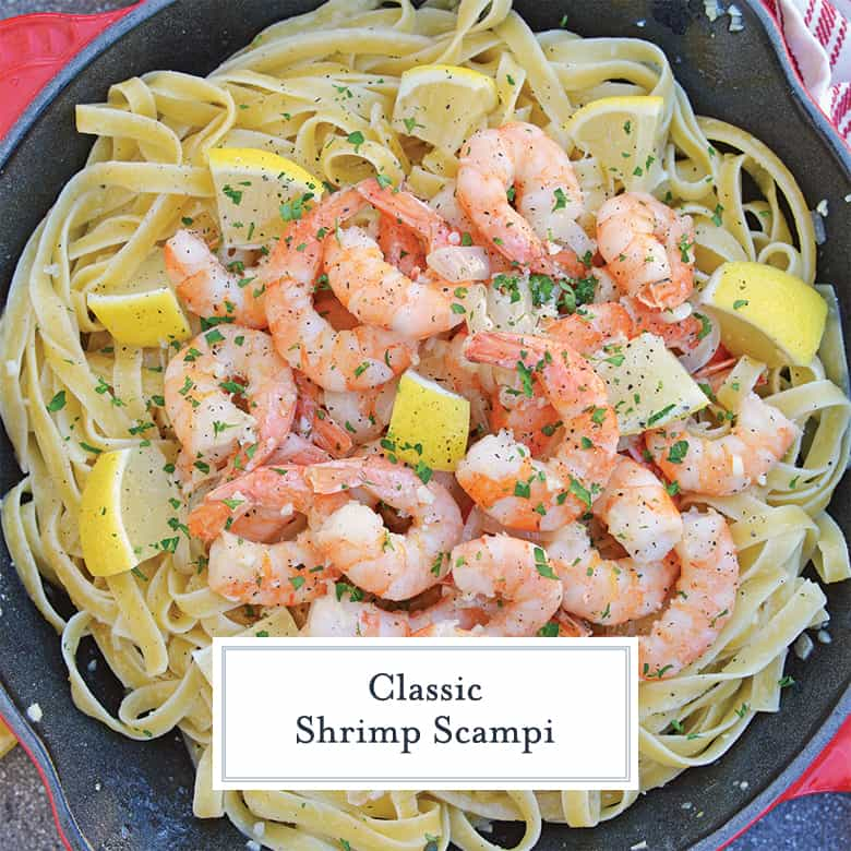 Shrimp Scampi in a red cast iron skillet with lemon wedges
