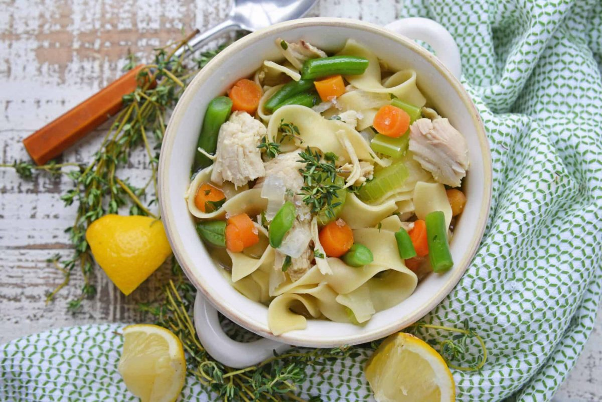 overhead of chicken noodle soup with lemon
