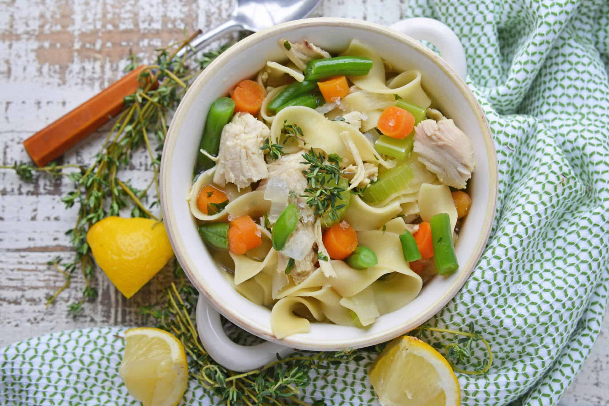 Chicken noodle soup in a white serving bowl