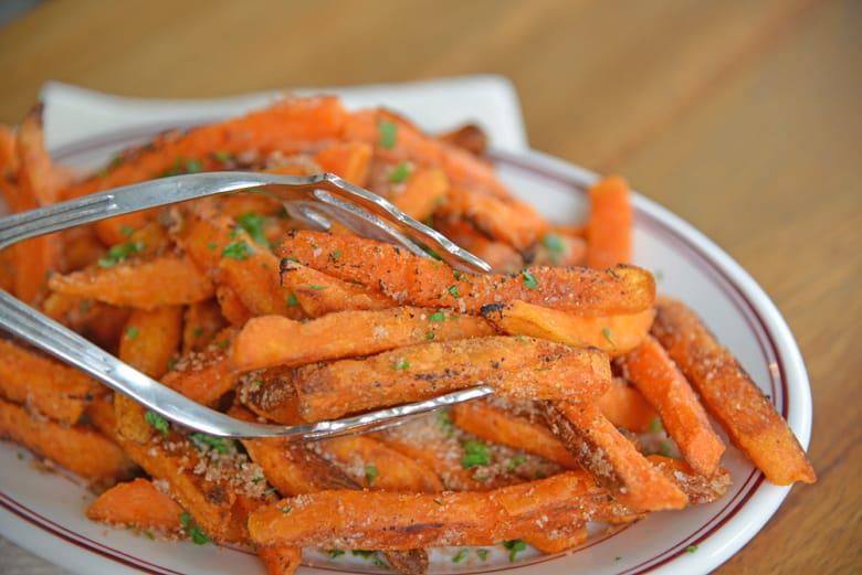 Sweet potato fries being served with large tongs