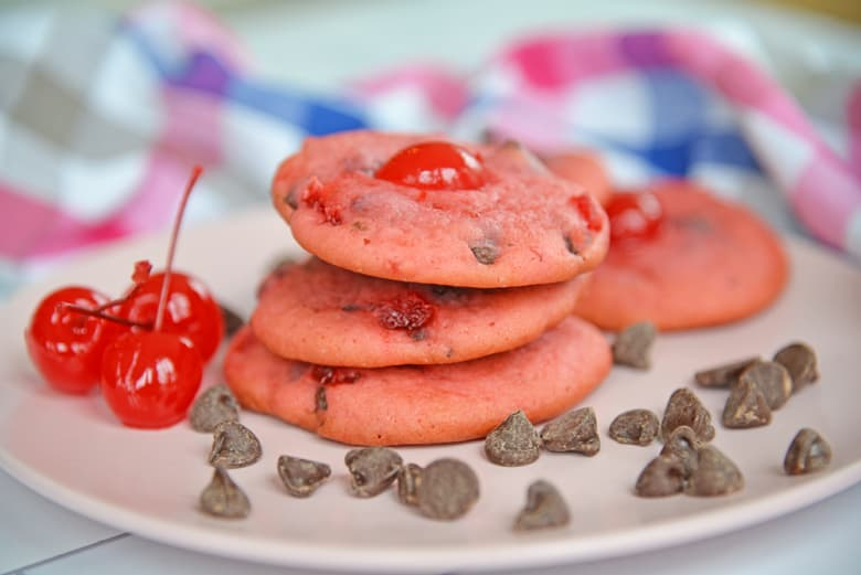 Stack of cherry chocolate chip cookies with maraschino cherries and chocolate chips