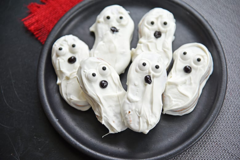 No bake ghost cookies on a black plate with red burlap background