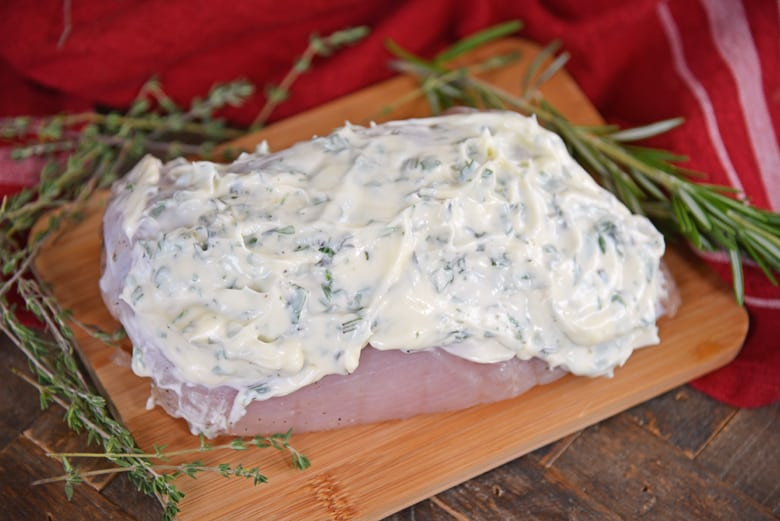 Herbed mayo slathered onto turkey breast on a cutting board