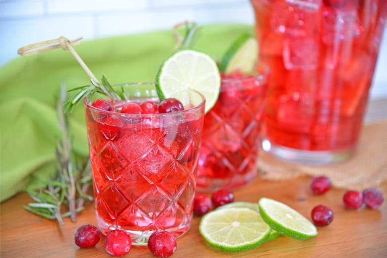 Side view of cocktail glass with cranberries, ice cubes and lime