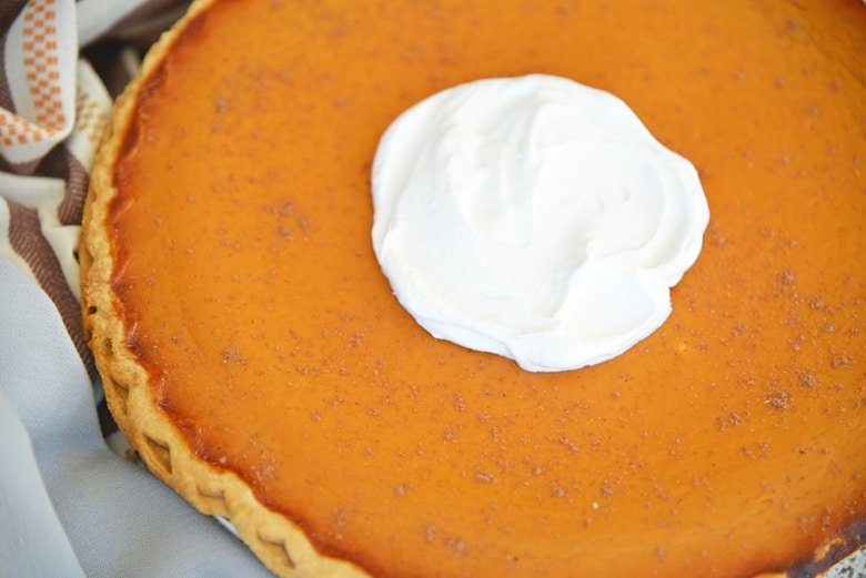 Angle view of whole pumpkin pie with whipped cream center