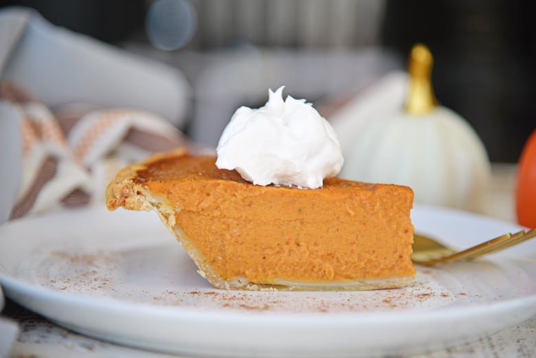 Side angle of pumpkin pie with whipped cream dollop