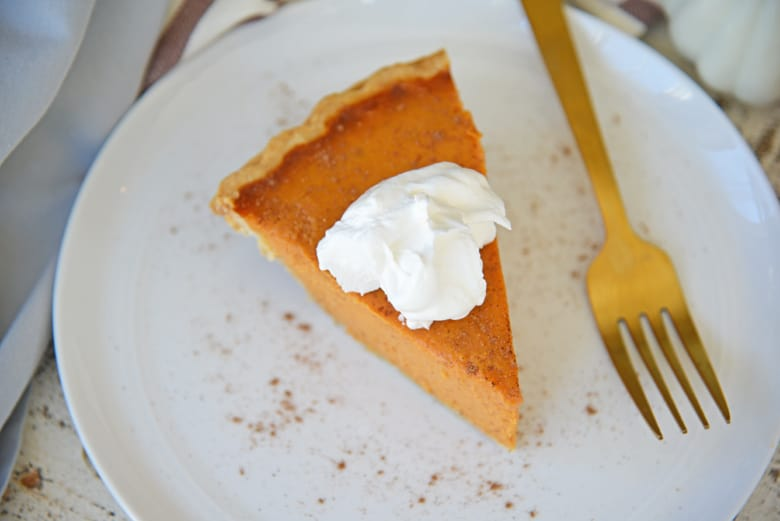 Slice of creamy pumpkin pie on a white plate with a gold fork