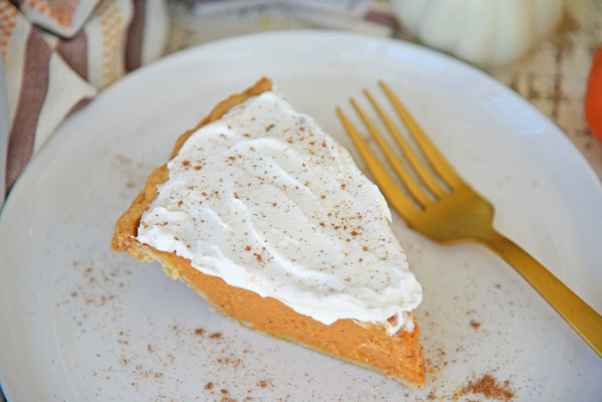 Slice of frosted pumpkin pie on a white plate with gold fork