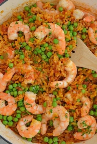 A bowl of food on a plate, with Paella