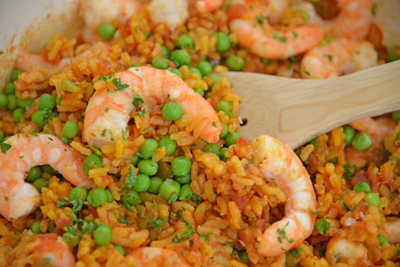 Wooden spoon with shrimp paella and peas