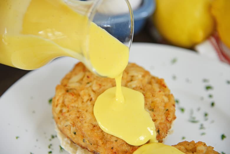 Hollandaise sauce pouring over a crab cake