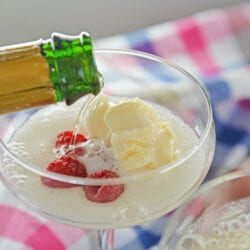 pouring champagne into a glass with ice cream and raspberries