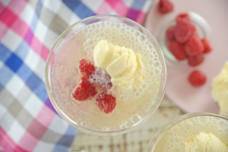 Overhead of champagne float with fresh raspberries