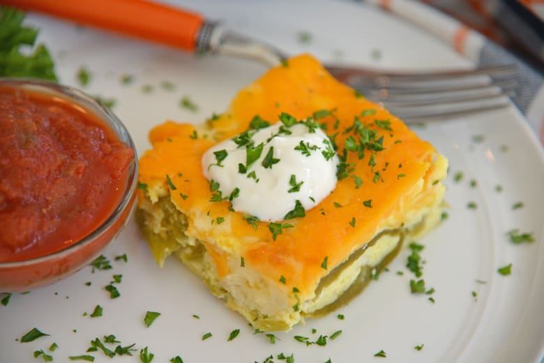 slice of chile relleno casserole with sour cream and salsa